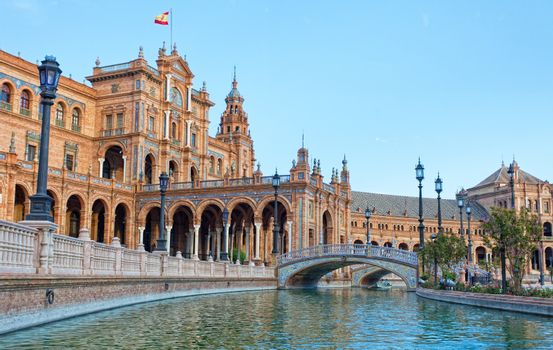 Tourists go boating on the channel on Plaza de Espana in Seville, Spain