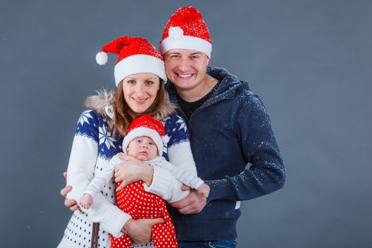 Christmas theme - Portrait of happy family with baby in Santa's hat in studio