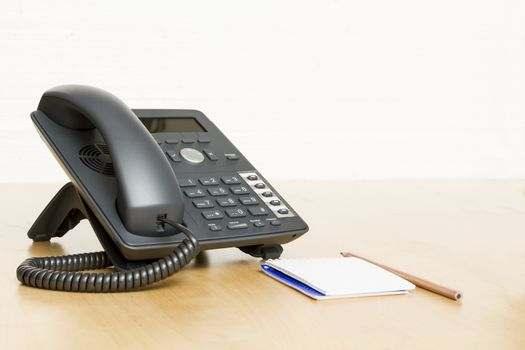 phone on desk with notepad in white background. Wooden desk.