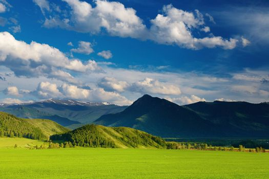 Mountain landscape with green field and cloudy sky