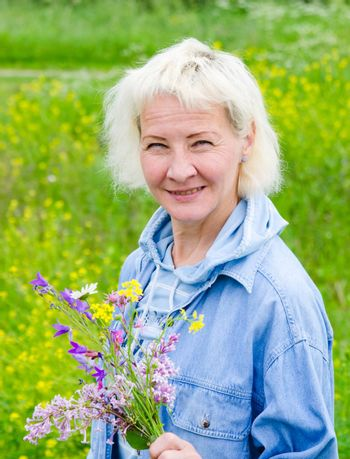 Portrait of a middle-aged woman with a bouquet of wild flowers