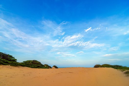 View of a sand dune and deep blue sky