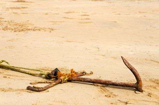 Old rusted anchor buried in sand