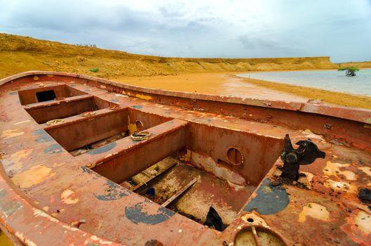 Old red boat and desert landscape in La Guajira, Colombia