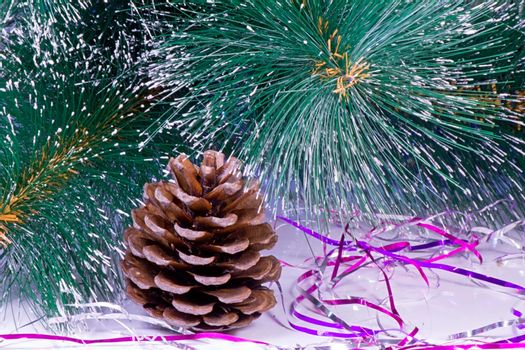 Near the branches of the tree is a pine cone and Christmas decorations