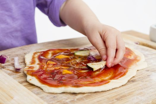 hand of young child making pizza on wooden board