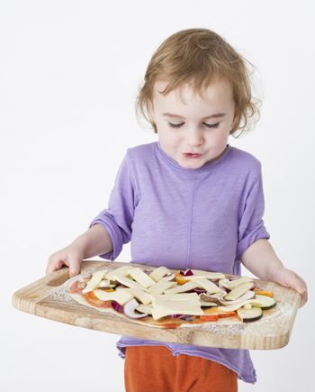 child carrying fresh pizza to the oven. studio shot in grey background