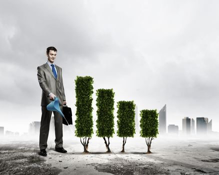 Image of businessman watering plant shaped like graph