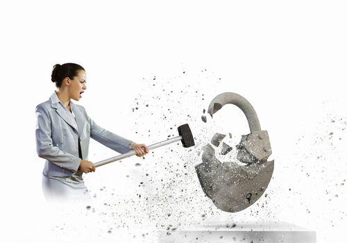 Image of businesswoman crashing lock with hammer