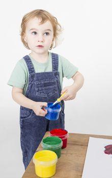 little girl with brush in paint tub. studio shot on light grey background
