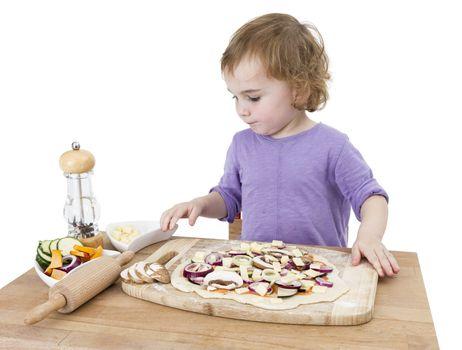 preschooler making fresh pizza on wooden desk. isolated on white background