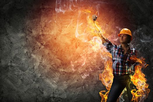 Image of woman in hardhat with torch in fire flames