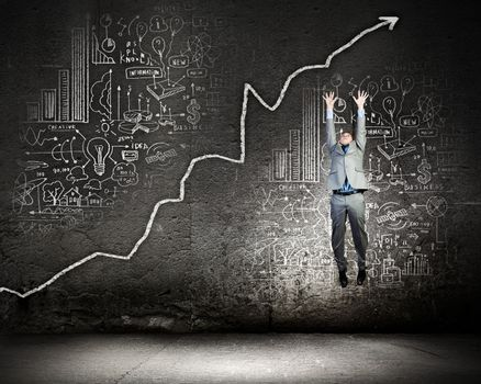 Image of young businessman jumping above graph
