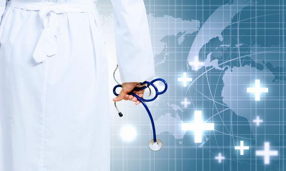 Image of human hand holding stethoscope against media background