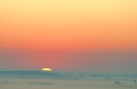 sunset on misty countryside