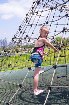 Girl climbing on rope ladder against sky
