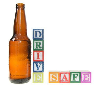 Letter blocks spelling drive safe with a beer bottle. Isolated on a white background