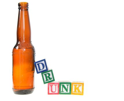 Letter blocks spelling drunk with a beer bottle. Isolated on a white background