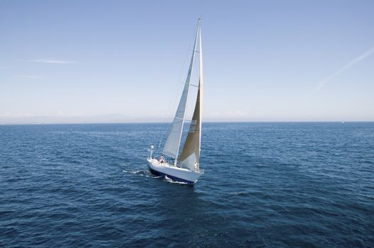 Sailboat at the peaceful blue ocean against the sky