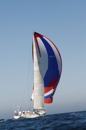 Yacht on ocean with full sail side view