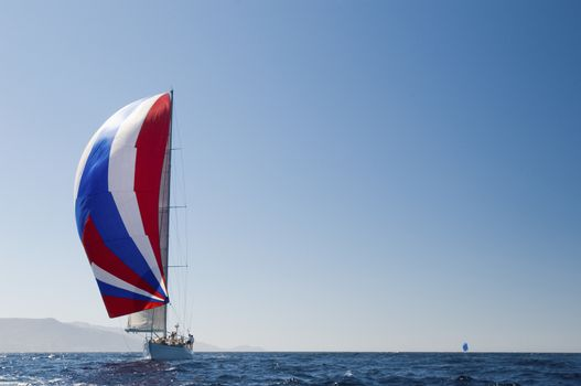 Yacht in the blue ocean with full sail against the clear sky