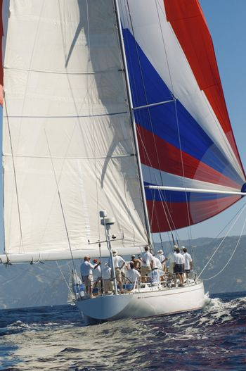 Yacht on ocean with full sail back view