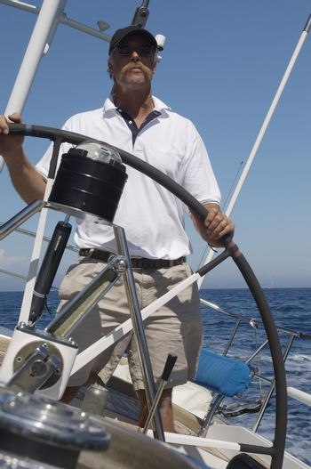 Middle aged man Steering a yacht against clear blue sky