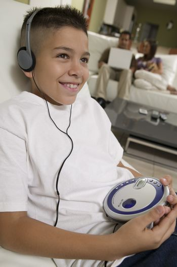 Boy Listening to Music on Portable CD Player in living room