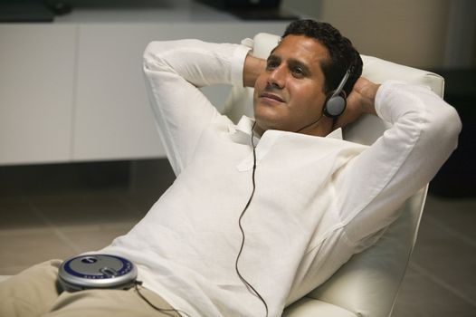 Man Reclining in living room Listening to portable CD player