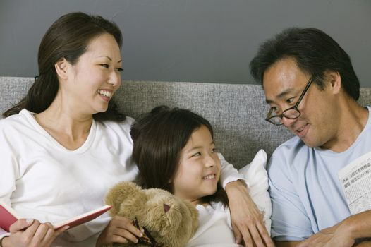 Mother and father relaxing in bed with daughter