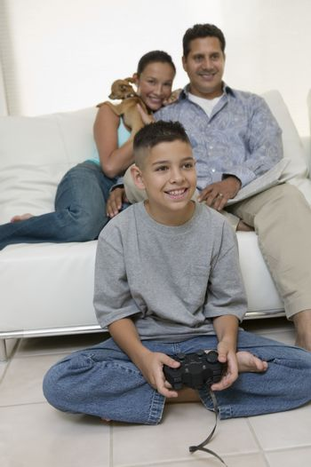 Parents Watching Son Play Video Games in living room front view