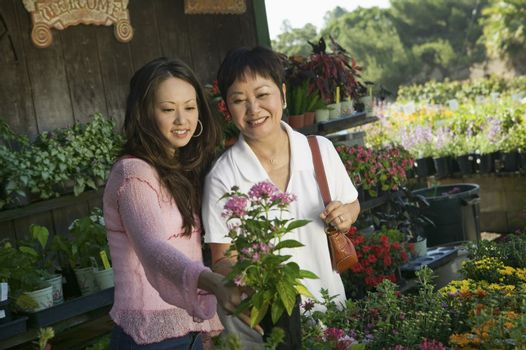Woman with mother looking at flowers in plant nursery