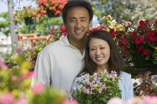 Couple holding plants in plant nursery portrait
