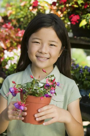 Young girl holding potted flowers in plant nursery portrait