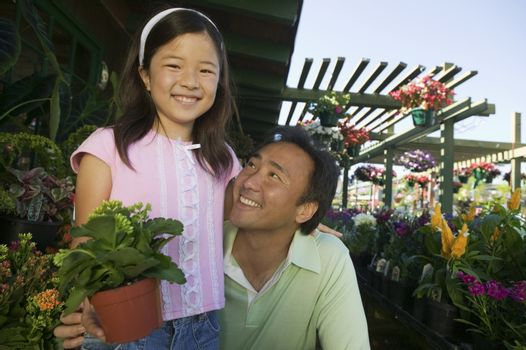 Father and Daughter in plant nursery portrait close up