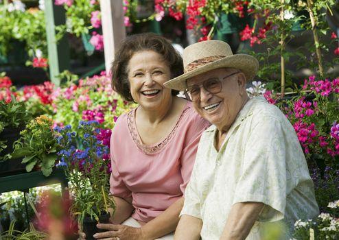 Portrait of happy couple selecting flowers in nursery