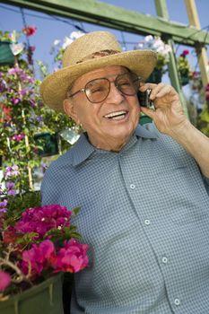 Senior Man standing in plant nursery Using Cell Phone