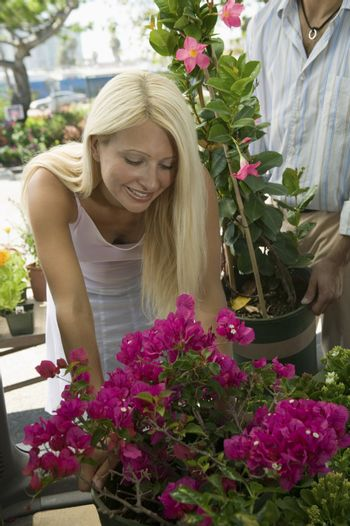 Blond young woman shopping for flowers at the plant nursery