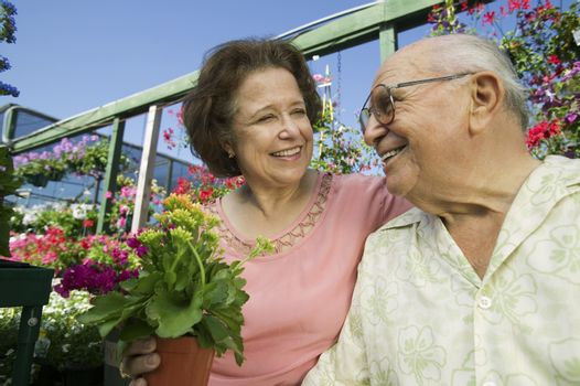 Closeup of a smiling senior couple among flowers at the plant nursery