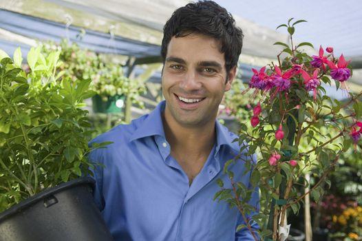 Man Carrying Plants in plant nursery portrait