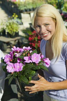 Woman Holding Flowers in plant nursery portrait