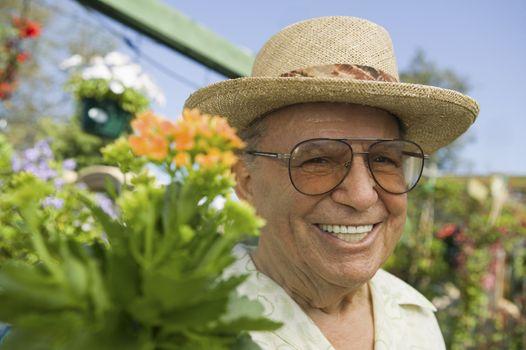 Senior Man standing in plant nursery portrait close up