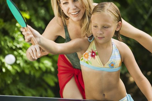 Little girl playing ping-pong with her happy mother outdoors