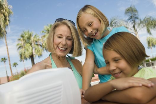 Two girls (7-9) and grandmother watching portable television outdoors.