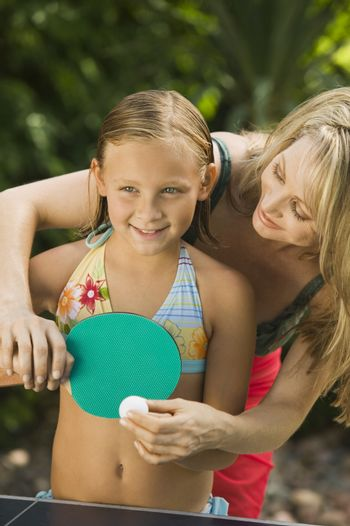 Mother teaching little daughter to play ping-pong outdoors