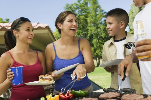 Cheerful Family Around The Grill At Picnic