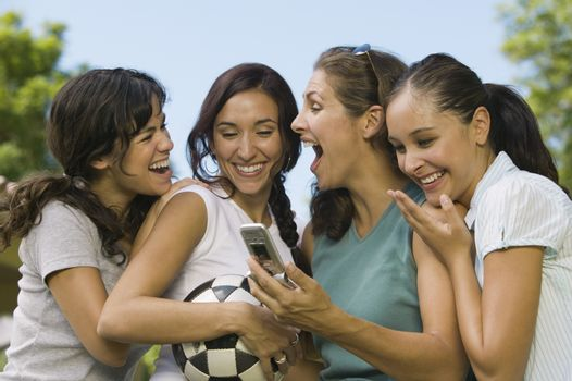 Four Women Laughing At Mobile Phone Display