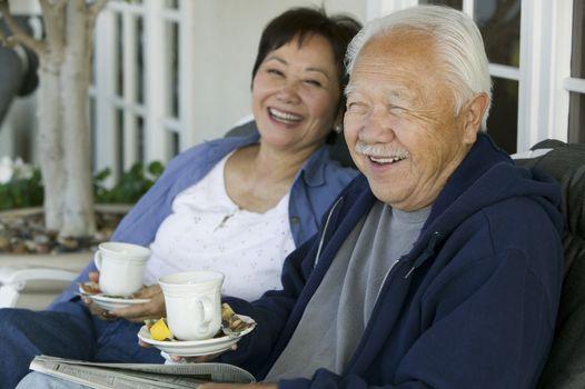 Senior couple drinking tea on porch smiling