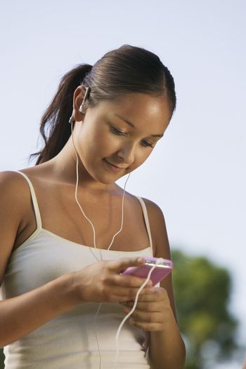 Young Woman listening to portable music player outdoors.