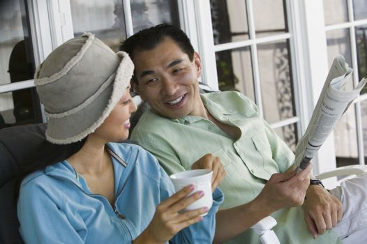 Couple drinking coffee and reading newspaper on porch